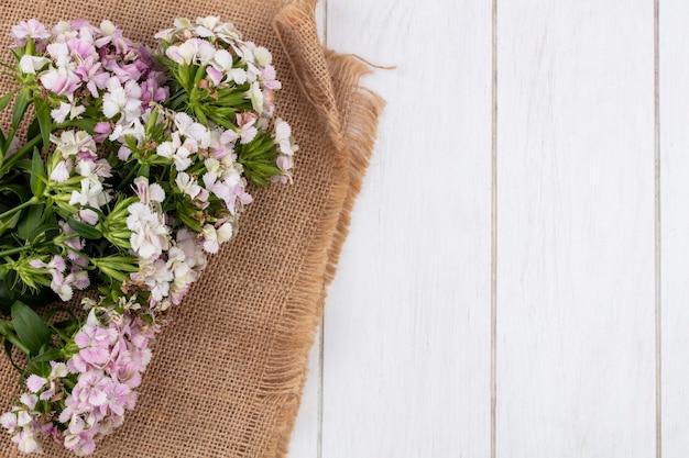 Bovenaanzicht van bloemen op een beige servet wit oppervlak Gratis Foto