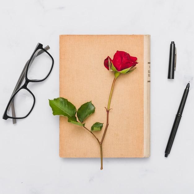Bovenaanzicht van boek en bloem Gratis Foto