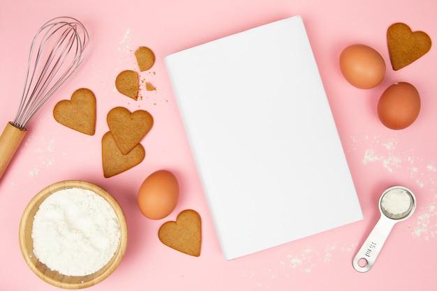 Bovenaanzicht van boek en koekjes op roze achtergrond Gratis Foto