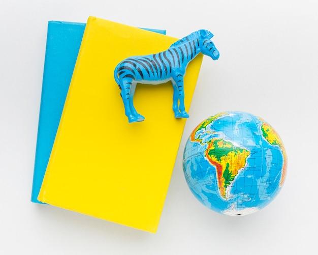 Bovenaanzicht van boek met zebra beeldje en planeet aarde voor dierendag Gratis Foto