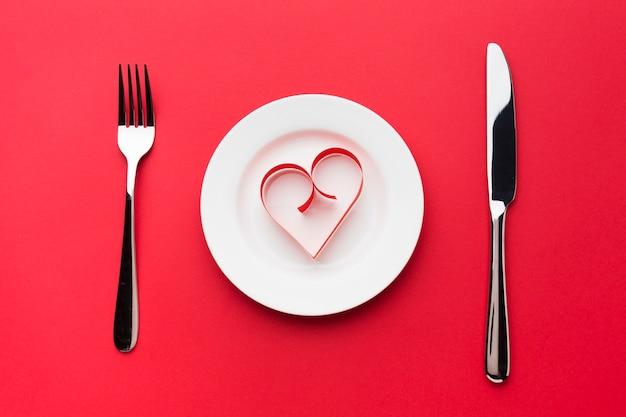 Bovenaanzicht van bord met papieren hartvorm en bestek Gratis Foto