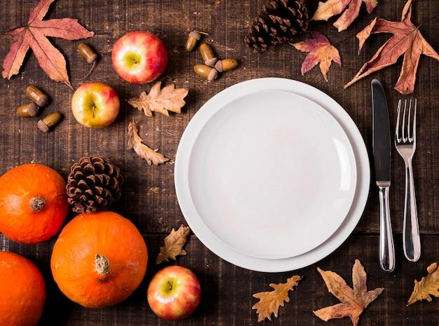 Bovenaanzicht van borden voor thanksgiving-diner met herfstbladeren Gratis Foto