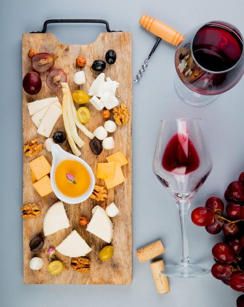 Bovenaanzicht van boter met verschillende soorten kaas druiven olijven noten op snijplank en glazen wijn met kurken en kurkentrekker op wit Gratis Foto