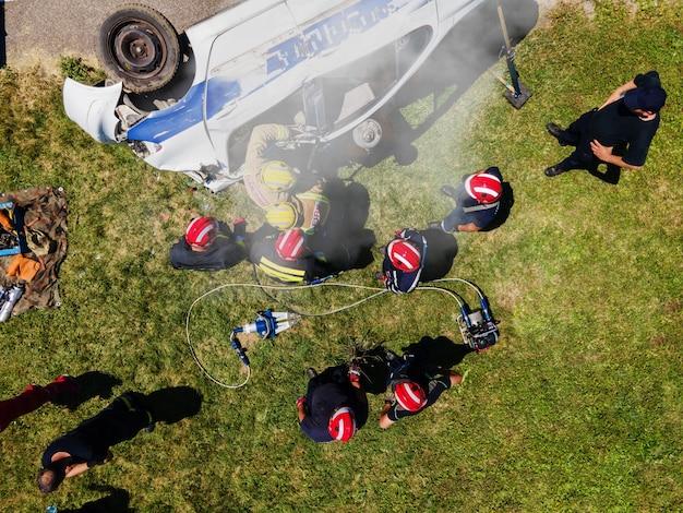 Bovenaanzicht van brandweerlieden die proberen de man in de gecrashte auto vrij te laten. Premium Foto