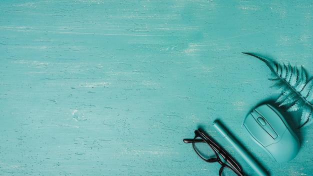 Bovenaanzicht van bril; pen; muis; varen op turkooizen achtergrond Gratis Foto