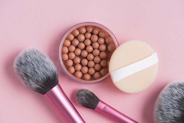 Bovenaanzicht van bronzing parels; spons en make-up borstels op roze achtergrond Gratis Foto