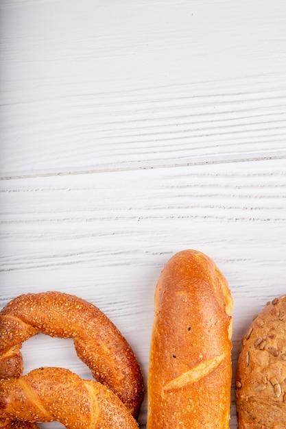 Bovenaanzicht van brood als bagel stokbrood op houten achtergrond met kopie ruimte Gratis Foto