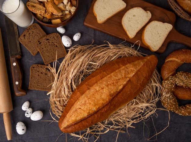 Bovenaanzicht van brood als stokbrood op rogge van stro en wit brood bagel met melk eieren op kastanjebruine achtergrond Gratis Foto