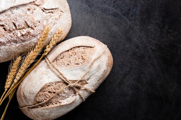 Bovenaanzicht van brood en tarwe op zwarte achtergrond Gratis Foto