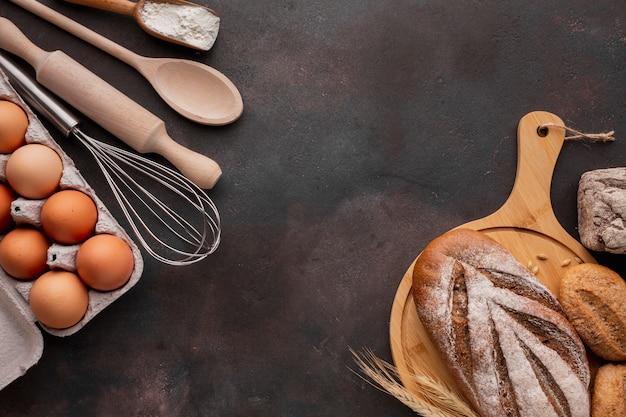 Bovenaanzicht van brood op een houten bord met eierdoos Gratis Foto