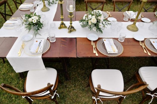 Bovenaanzicht van bruine chiavari stoelen, glaswerk en bestek op de houten tafel buiten, met witte eustomas boeketten Gratis Foto