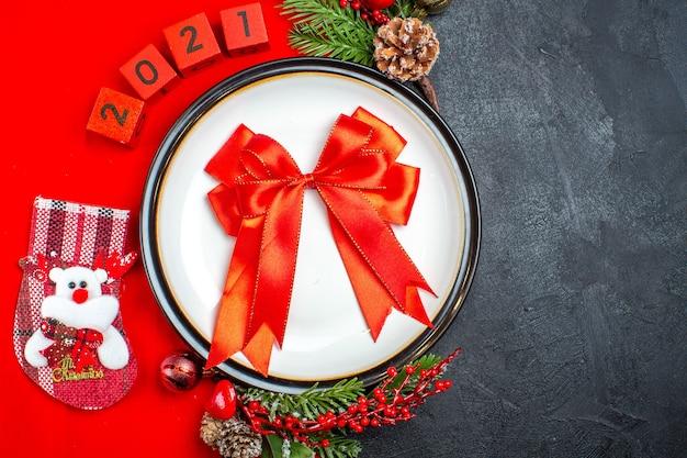 Bovenaanzicht van cadeau met lint op diner plaat decoratie accessoires fir takken en nummers kerst sok op een rode servet op een zwarte achtergrond Gratis Foto