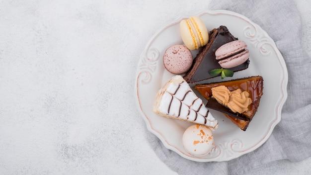 Bovenaanzicht van cake op plaat met kopie ruimte en macarons Gratis Foto