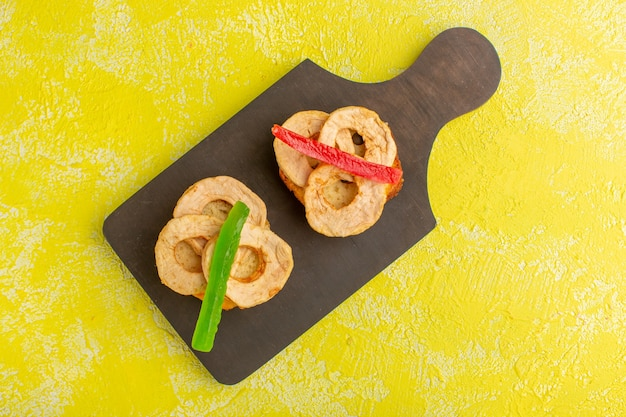 Bovenaanzicht van cakeplakken met gedroogde ananasringen en marmelade op geel oppervlak Gratis Foto
