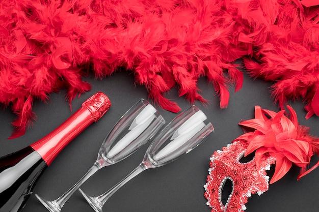 Bovenaanzicht van carnaval maskers met veren en champagnefles Gratis Foto