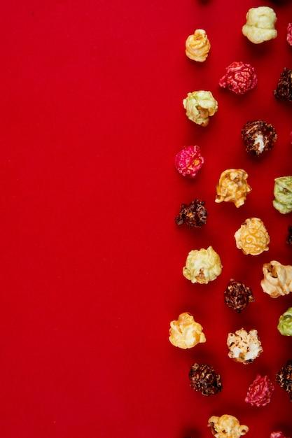 Bovenaanzicht van chocolade en kegels popcorn aan de rechterkant en rood met kopie ruimte Gratis Foto