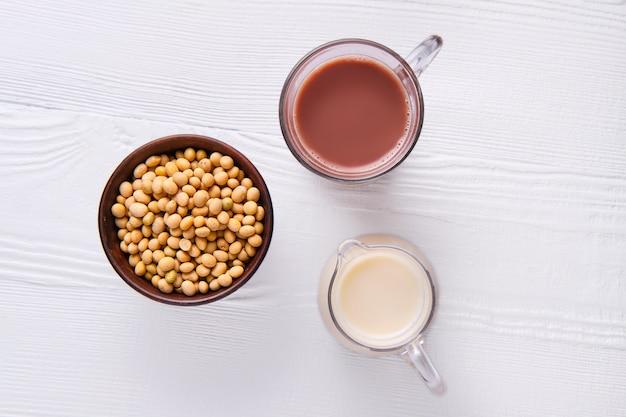 Bovenaanzicht van chocolademelk en sojamelk in glas op witte tafel Premium Foto