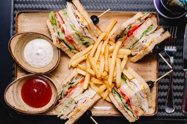Bovenaanzicht van club sandwich geserveerd met frietjes ketchup en mayonaise Gratis Foto
