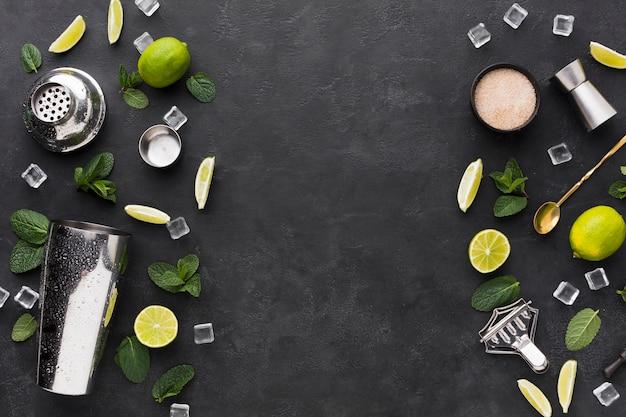 Bovenaanzicht van cocktail essentials met shaker en ijsblokjes Gratis Foto