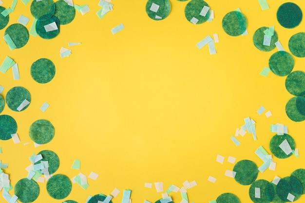 Bovenaanzicht van confetti frame op gele achtergrond met kopie ruimte Gratis Foto