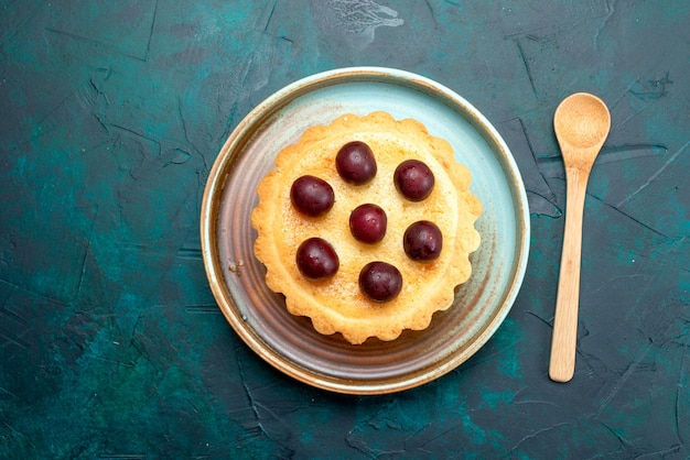 Bovenaanzicht van cupcake met zure kersen naast lepel op donkerblauw, Gratis Foto