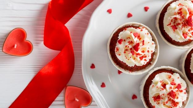 Bovenaanzicht van cupcakes met hartvormige kaarsen en lint Gratis Foto