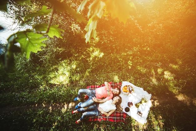 Bovenaanzicht van de gelukkige paar liggend op het gras op een zonnige dag Gratis Foto