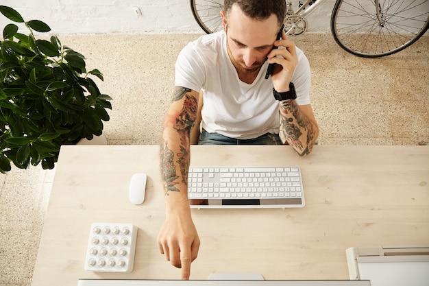 Bovenaanzicht van de getatoeëerde man toont iets te zien terwijl hij aan de telefoon spreekt op zijn werkende desktop in het co-working center Gratis Foto
