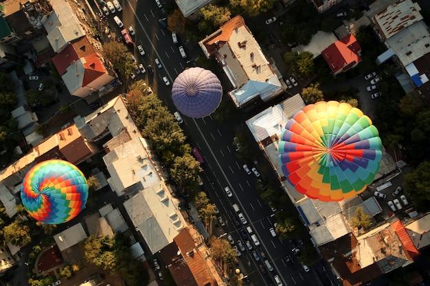 Bovenaanzicht van de heteluchtballonnen over de oude gebouwen van een stad Gratis Foto