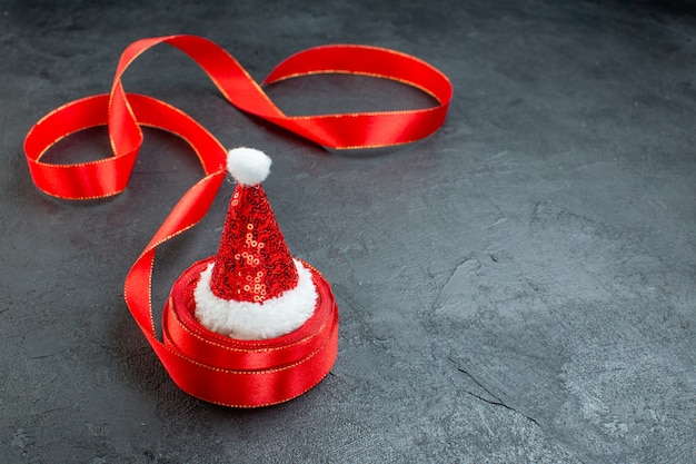 Bovenaanzicht van de kerstman hoed op een rol lint aan de rechterkant op donkere achtergrond Gratis Foto