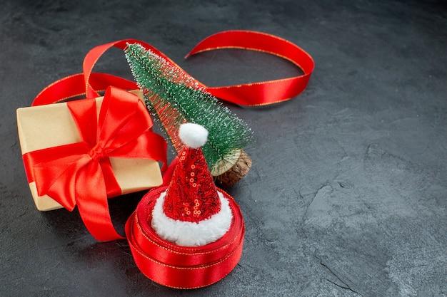 Bovenaanzicht van de kerstman hoed op een rol lint en mooie cadeau kerstboom op donkere achtergrond Gratis Foto