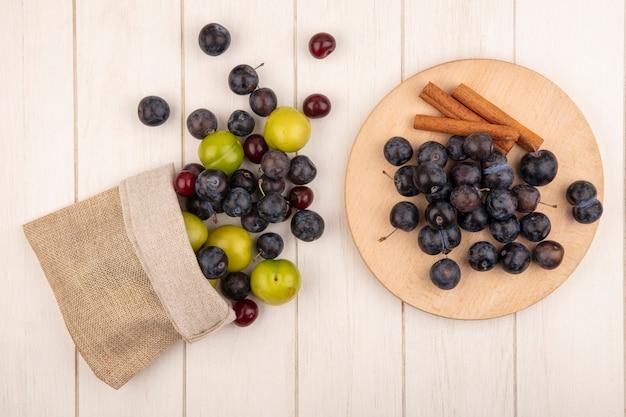 Bovenaanzicht van de kleine zure blauw-zwart fruit sleepruimen op een houten keukenbord met kaneelstokjes met groene kersenpruim en rode kersen die uit een jutezak vallen op een witte houten achtergrond Gratis Foto