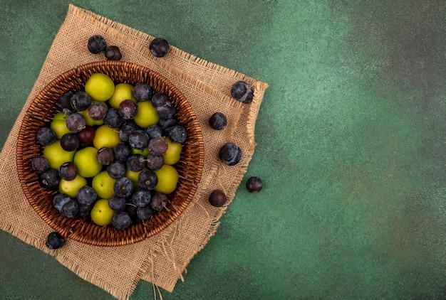 Bovenaanzicht van de kleine zure blauwzwarte fruit sleepruimen met groene kersenpruim op een emmer op een zakdoek op een groene achtergrond met kopie ruimte Gratis Foto