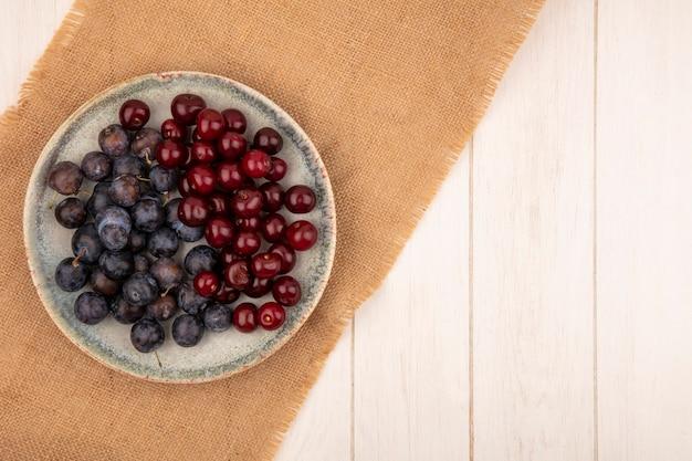 Bovenaanzicht van de kleine zure blauwzwarte fruit sleepruimen met rode kersen op een bord op een zakdoek op een witte achtergrond met kopie ruimte Gratis Foto