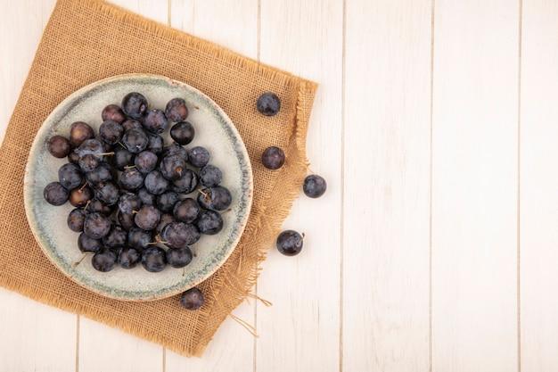 Bovenaanzicht van de kleine zure blauwzwarte fruitslaes op een kom op een zakdoek op een witte achtergrond met kopie ruimte Gratis Foto
