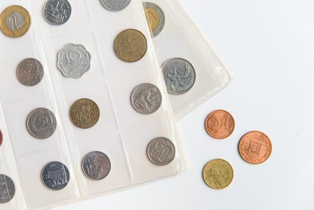 Bovenaanzicht van de numismatische albumbladen en munten. collectie van zeldzame munten op de witte achtergrond met kopie ruimte Premium Foto