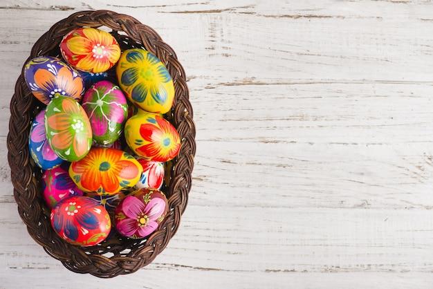 Bovenaanzicht van de paashaas eieren op een rieten mand Gratis Foto
