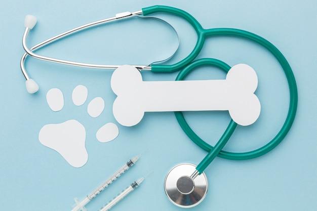 Bovenaanzicht van de stethoscoop met papierbeen en pootafdruk voor dierendag Gratis Foto