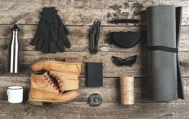 Bovenaanzicht van diverse hulpmiddelen voor wandeluitrusting op grunge hout Premium Foto