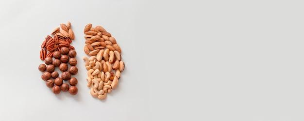 Bovenaanzicht van diverse noten op grijze achtergrond met kopie ruimte op grijs Premium Foto