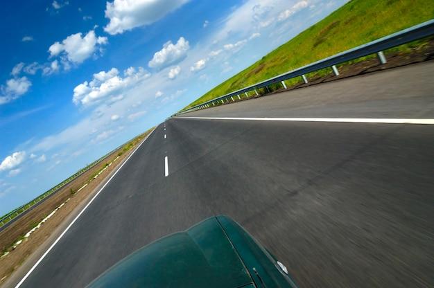 Bovenaanzicht van een auto is een gladde snelweg omgeven door mooie zomerse natuur met velden met groene bomen en blauwe lucht op een zonnige warme zomerdag Premium Foto
