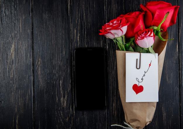 Bovenaanzicht van een boeket van rode rozen in ambachtelijke papier met briefkaart in bijlage en een smartphone op donkere houten achtergrond met kopie ruimte Gratis Foto