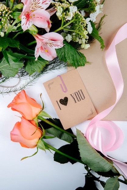 Bovenaanzicht van een boeket van roze kleur alstroemeria bloemen met bloeiende viburnum en een ansichtkaart met koraalkleurige rozen op witte achtergrond Gratis Foto