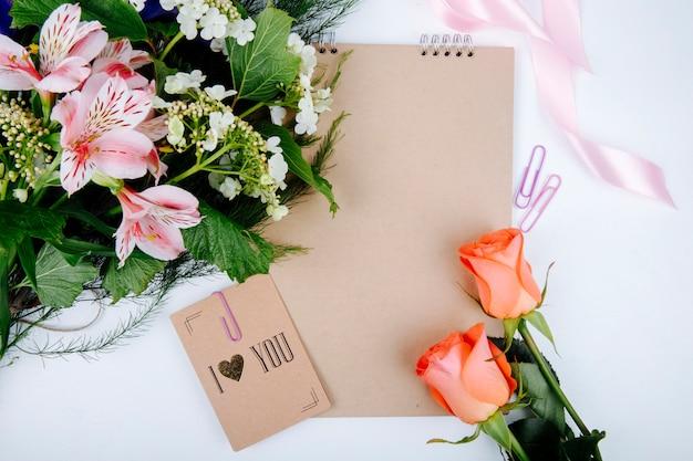 Bovenaanzicht van een boeket van roze kleur alstroemeria bloemen met bloeiende viburnum en een schetsboek met een ansichtkaart en koraalkleurige rozen op witte achtergrond Gratis Foto
