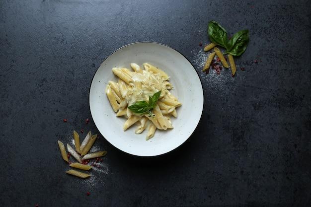 Bovenaanzicht van een bord pasta met kaassaus en basilicum op de zwarte tafel Gratis Foto
