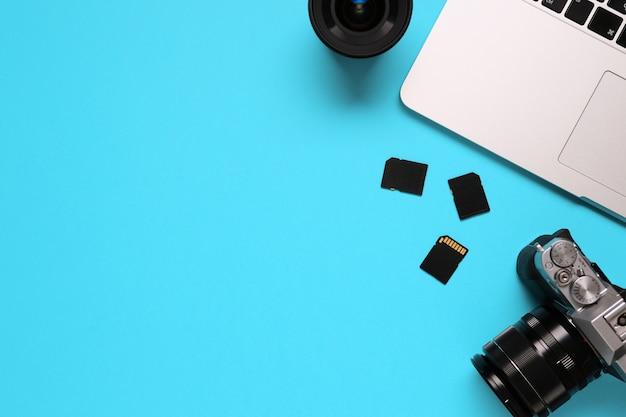 Bovenaanzicht van een desktop van een fotograaf bestaande uit een camera, een laptop, een notebook en een geheugenkaart op een blauwe achtergrond van het bureau - kopieer de ruimte. Premium Foto