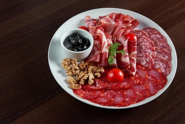 Bovenaanzicht van een diverse salami vlees plaat geserveerd met zwarte olijven en walnoten op tafel Gratis Foto