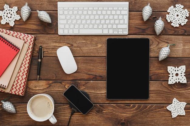 Bovenaanzicht van een houten bureaublad met computer met kantoorbenodigdheden en kerstversiering Premium Foto