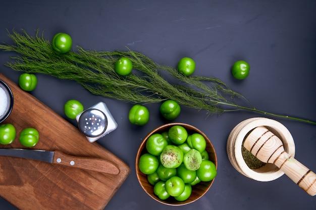 Bovenaanzicht van een houten snijplank met een mes, zoutvaatje, gedroogde pepermunt in een vijzel, venkel en zure groene pruimen in een houten kom op zwarte tafel Gratis Foto