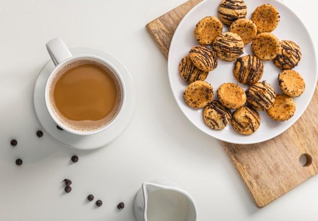 Bovenaanzicht van een koffiekopje met plaat van koekjes Gratis Foto